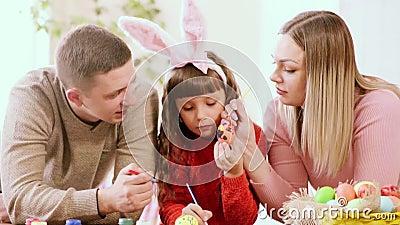 A filha guarda um ovo da galinha, e seus pais decoram-no vídeos de arquivo