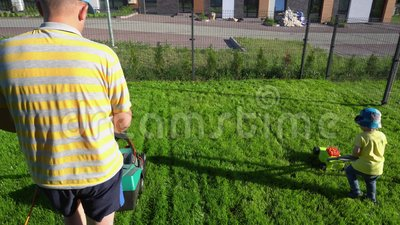 Filho que empurra um cortador de grama do brinquedo quando o paizinho segar com o seu Tiro da suspens?o Cardan vídeos de arquivo