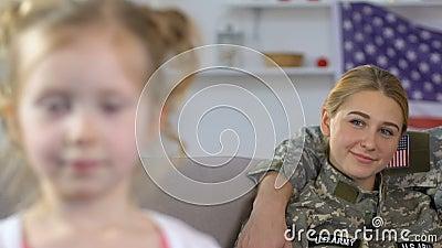 Fille adorable regardant in camera, parents militaires fiers reposant le sofa, patriotisme banque de vidéos