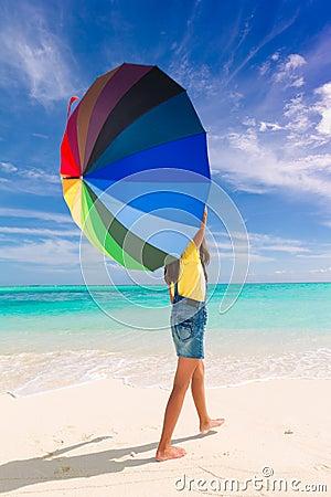 Fille avec le parapluie sur la plage