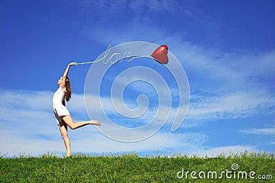Fille avec un ballon rouge sous forme de coeur