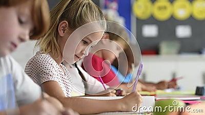 Fille blonde de sourire faisant des devoirs clips vidéos