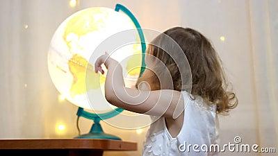 Fille d'enfant jouant avec un globe lumineux Le bébé étudie la géographie et une carte du monde banque de vidéos