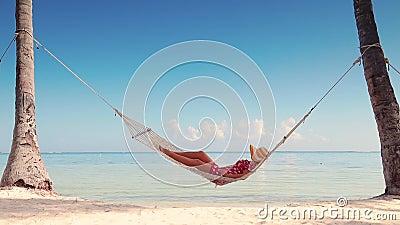 Fille d?tendant dans un hamac sur la plage tropicale d'?le Vacances d'?t? banque de vidéos