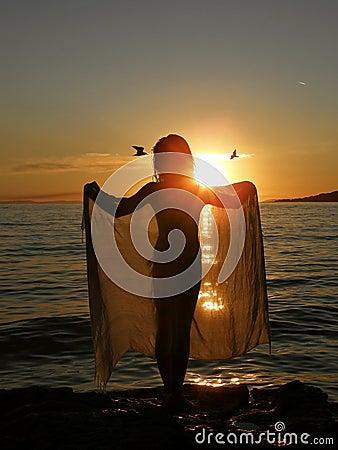 Fille dans le coucher du soleil avec l écharpe et les oiseaux