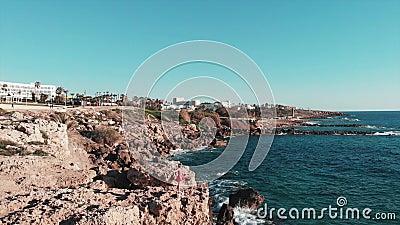 Fille dans les supports rouges de robe sur les falaises rocheuses avec des bras aux côtés Vagues fortes blanches de mer frappant  banque de vidéos
