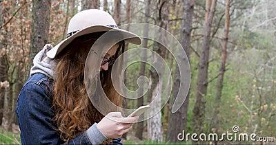 Fille dans un chapeau avec un téléphone dans une forêt conifére banque de vidéos