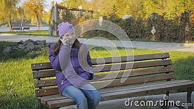 Fille de l'adolescence mignonne souriant et parlant au téléphone en parc d'automne se reposant sur le banc Supports dentaires Au  clips vidéos