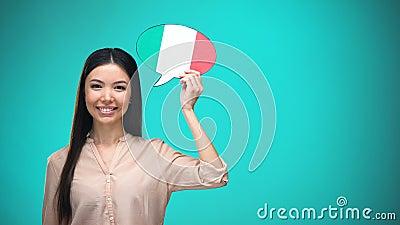 Fille de sourire tenant la bulle italienne de la parole de drapeau, apprenant la langue, idées de voyage banque de vidéos