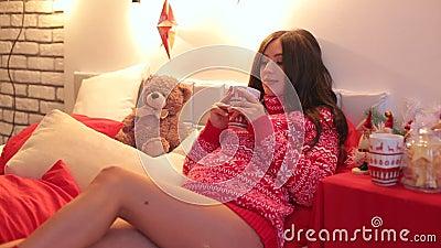 Fille enceinte avec une tasse de thé sur le ` s Ève de nouvelle année banque de vidéos