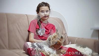 Fille et un crabot la fille s'assied sur le divan regardant TV, les mensonges de chien sur le recouvrement égalisant à l'intérieu banque de vidéos