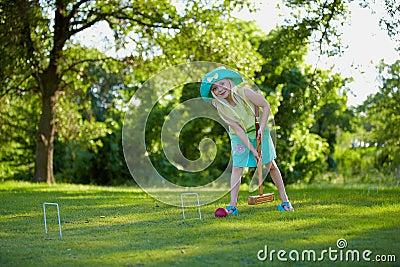 Fille jouant le jeu de croquet