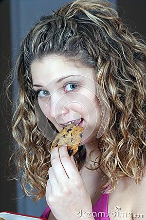 Fille mangeant le biscuit de chocolat