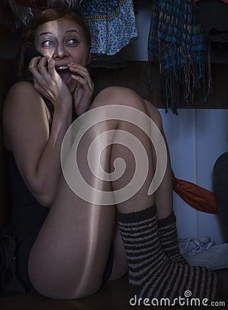 Fille se cachant dans le cabinet