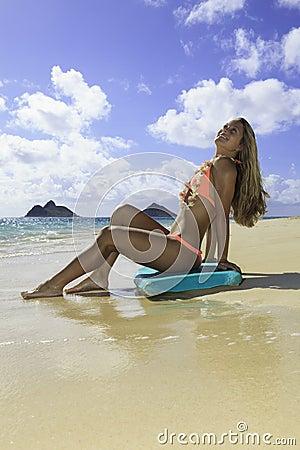 Fille sur la plage avec le panneau de boogie