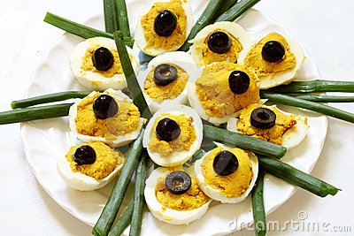 Filled eggs with olives on top