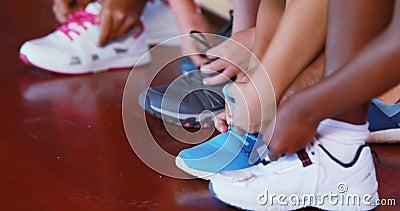 Filles attachant des dentelles de chaussure au terrain de basket banque de vidéos