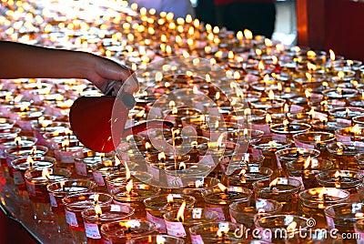 Filling up oil lamps on Wesak celebration