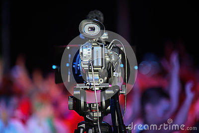 Film camera in front of a cheering crowd