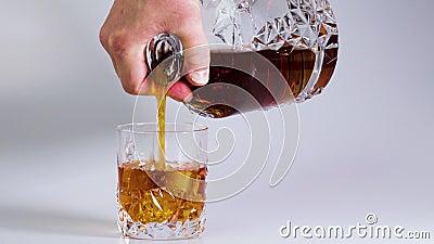 Film krótkometrażowy pokazujący whiskey wlewaną do szklanki z lodem na białym tle Wspaniałe tła zbiory