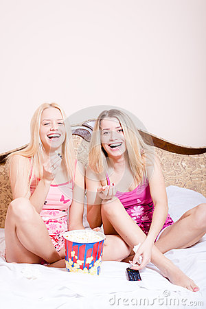 Film time: Two girl friends or sisters blond adorable attractive pretty young women sitting in bed with popcorn, watching movie