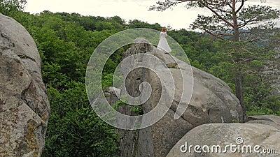 Filmagem aérea, Bride está na borda do abismo Alto penhasco à volta da noiva A câmera voa e voa lentamente filme