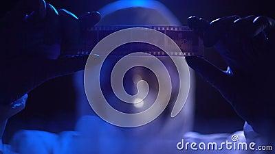 Filmstrip ассистента лаборатории наблюдая, ища доказательство против преступника видеоматериал