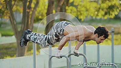 Fim acima do desportista que faz exerc?cios em barras paralelas no campo atl?tico video estoque