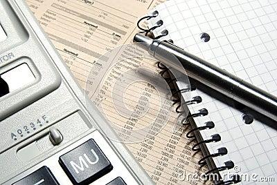 Financial calculator, steel pen and notebook.
