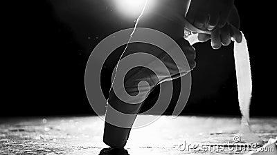 Fine sulle mani femminili che legano le scarpe del pointe sulla gamba isolata in riflettore su fondo nero Colpo in bianco e nero