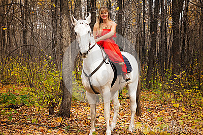 Fine young woman on horseback on white horse