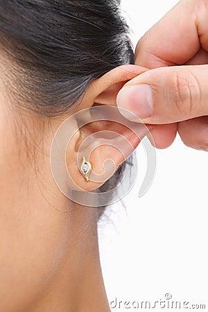 Finger, der Ohr der Frau klemmt