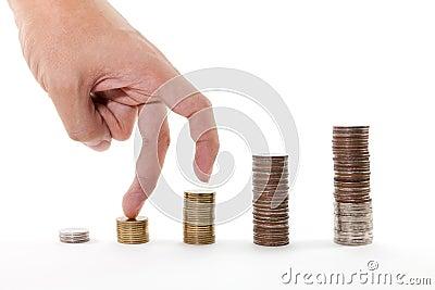 Finger, die oben auf Stapel Münzen auf weißem Hintergrund gehen