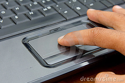 Finger on notebook touchpad.