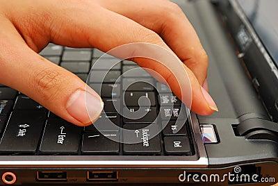 Finger pressing power button on laptop