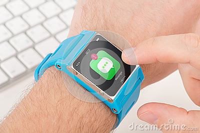 Finger taps messenger icon on blue smart watch