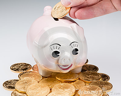 Hand placing gold coin into piggy bank