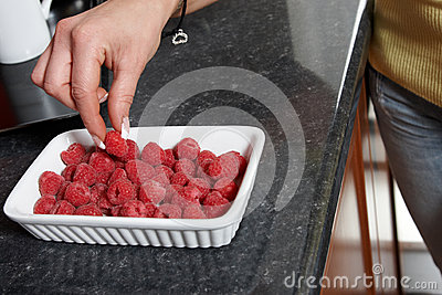 Fingers in the raspberry bowl
