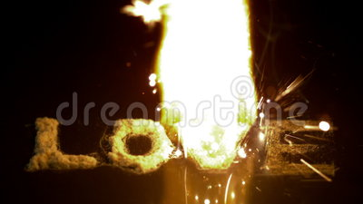 Fire burning up the word love on black surface stock video