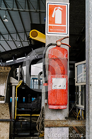Free Fire Extinguisher Tank Is Very Old. Hanging On A Pole In The Fac Royalty Free Stock Photography - 90407617