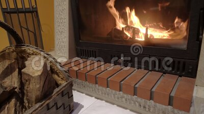 Fire in the home fireplace with firewood, pillows and poker in the foreground.  stock footage
