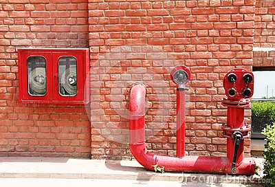 Fire hydrant,hose and pipes inserted on brick wall
