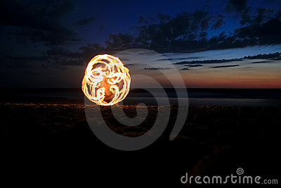 Fire poi on beach in sunset