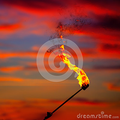 Fire torch at sunset sky with red clouds