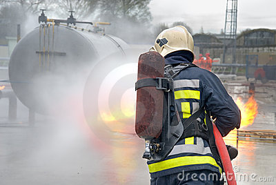 Firefighter extinguishing tank fire