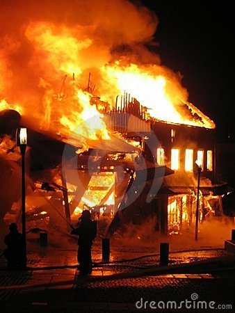 Firefighter fighting burning house.