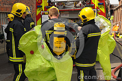 Firefighters in breathing apparatus don protective suits. Editorial Stock Image