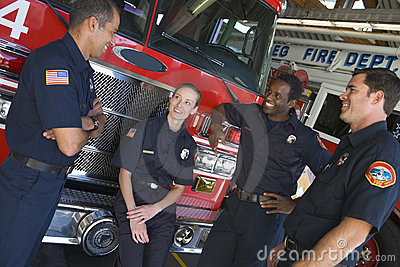Firefighters chatting by a fire engine