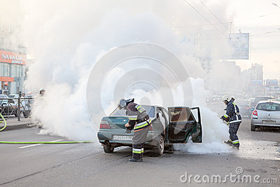 Firefighters extinguish burned car in city Editorial Stock Photo