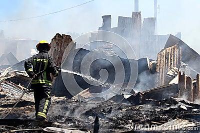 Fireman Hosing Remains of Shack House